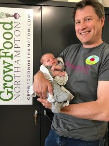Clem Clay holding his baby, with a Grow Food Northampton sign in the background