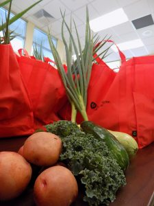 Potatoes, lettuce, zucchini, and fresh garlic in front of Red Harvard Pilgrim Foundation Bags full of these vegetables.
