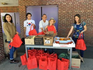 A woman and a boy picking up their Harvard Pilgrim Red Bags full of vegetables from a stand in front of Jackson St. School, two staff members of Grow Food Northampton and a volunteer filling the bags with vegetables