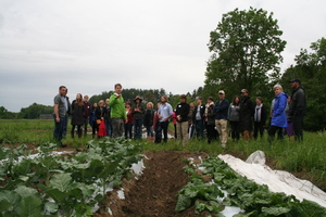 In the foreground, rows of leafy greens grow from the ground. Farmer Nate is in the background, gesturing to the field while talking. A group of people stand behind him in a semi-circle, listening.