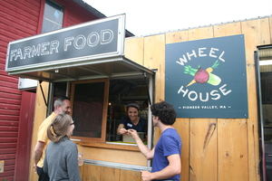 Woman in Wheelhouse food truck handing a radish out of the window to a man who reaches out to grab it. Two other attendees stand nearby watching.