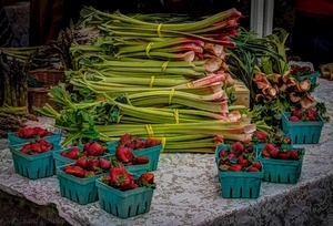Boxes of strawberries and bunches of green leafy vegetables at a farm stand at the Tuesday Market