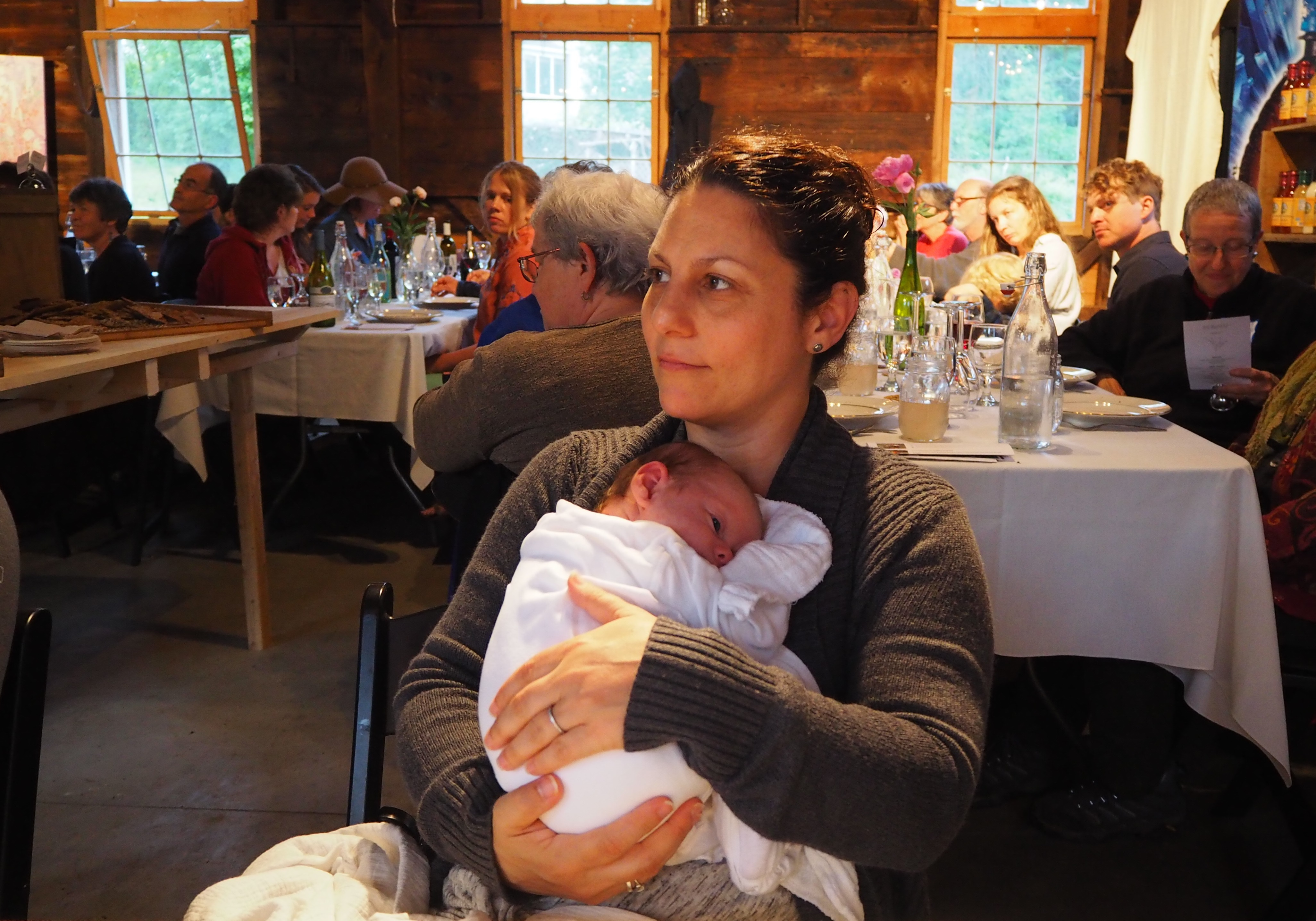Tiffany Seated Holding Her Baby Swaddled In White, With People In Background Seated At Dinner Tables